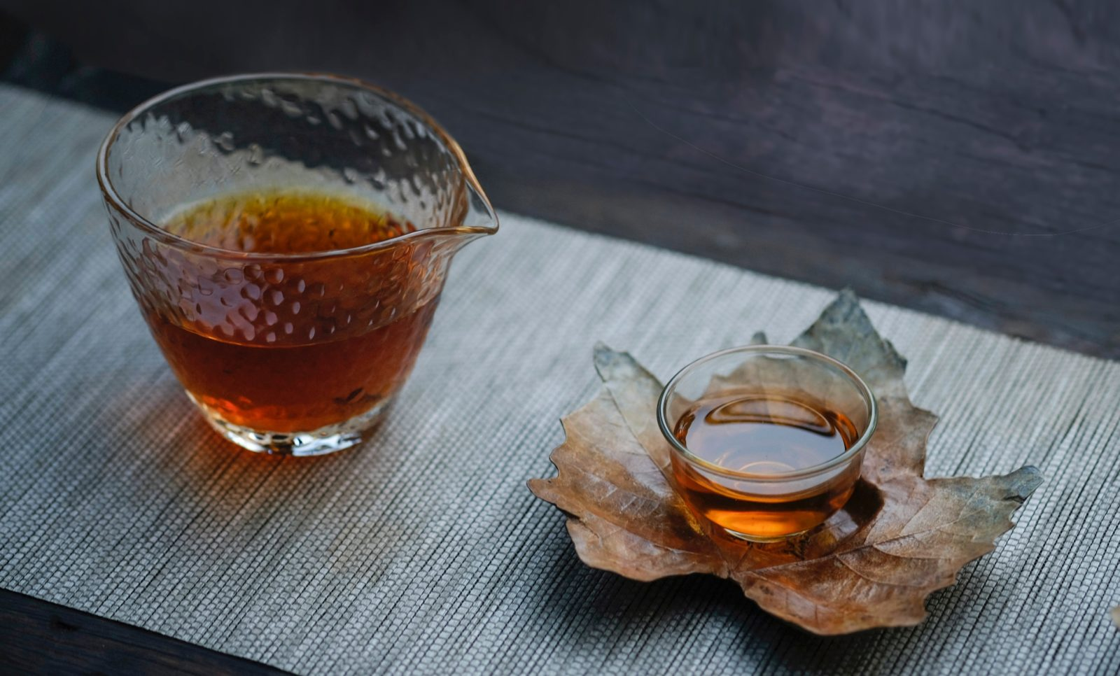 A cup of Chinese tea beside a ceramic leaf with another cup of tea resting on it.
