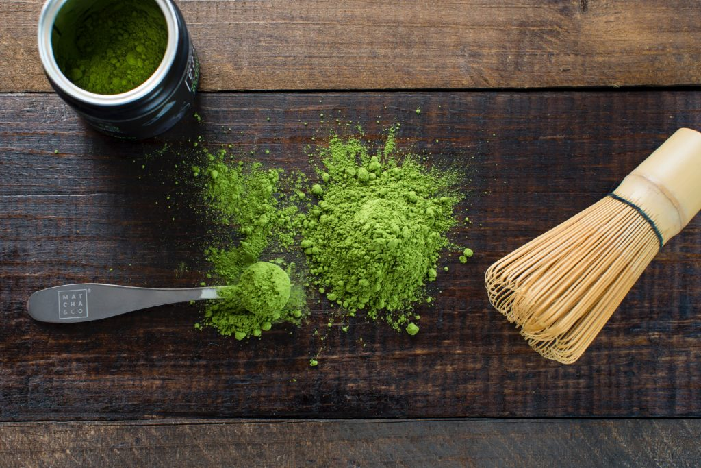 Matcha tea on a table with a brush, a cup and a spoon
